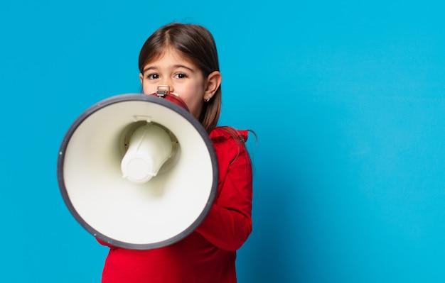 Ładna mała dziewczynka zły wyraz twarzy i trzymająca megafon