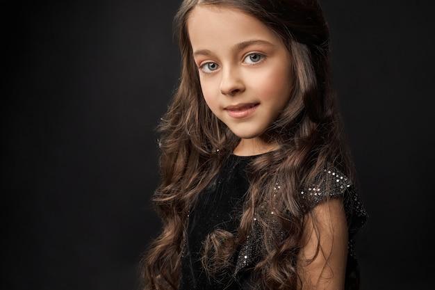 Ładna, mała modelka o długich, kręconych włosach pozuje w studio.