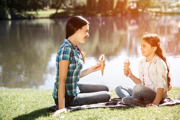 Ładna mama i jej córka siedzą twarzą w twarz w parku nad małym jeziorem