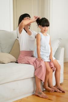 Ładna mama siedzi na kanapie i robi fryzurę dla uroczej dziewczyny.