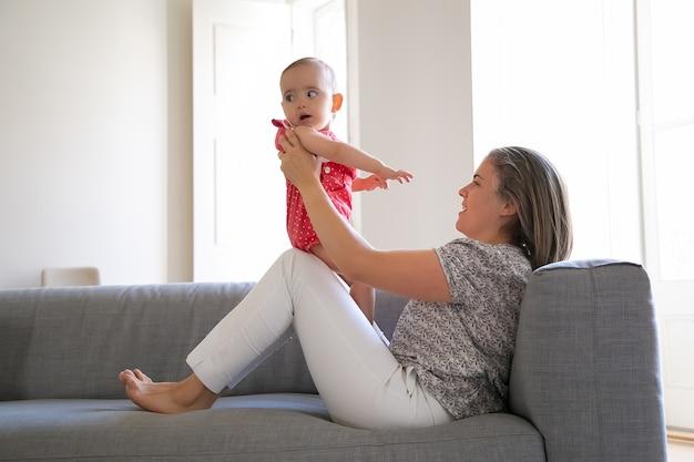 Ładna matka siedzi na kanapie i trzyma swoją córeczkę na kolanach. urocza dziewczynka patrząc od hotelu. długowłosa mama kaukaska bawi się z niemowlakiem i uśmiecha się. pojęcie rodziny i macierzyństwa