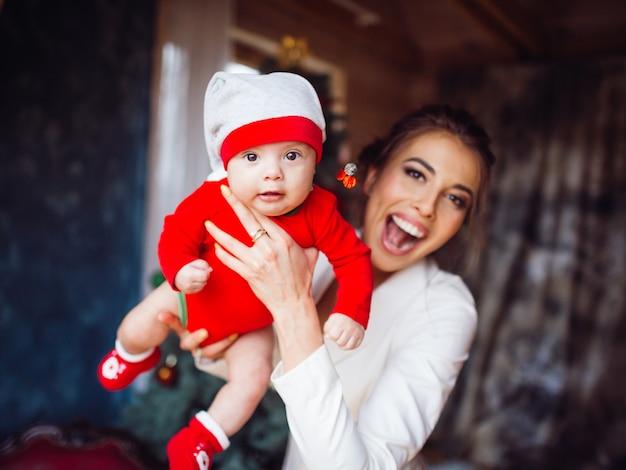 Ładna matka trzyma na rękach swoją córkę