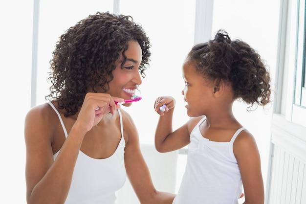 Ładna matka z jej córką szczotkuje ich zęby