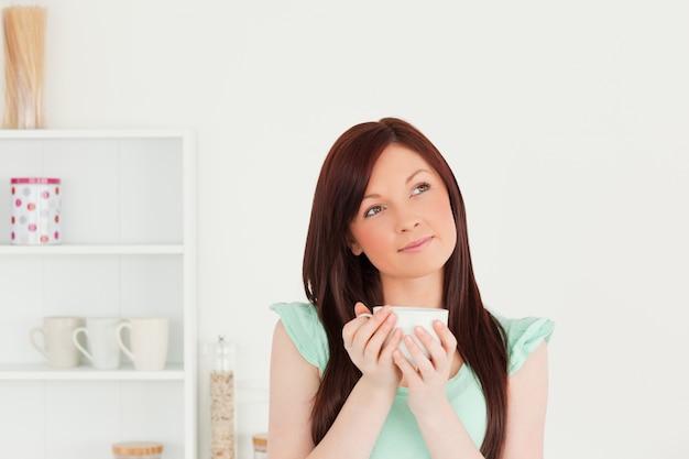 Ładna miedzianowłosa kobieta cieszy się jej śniadanie w kuchni
