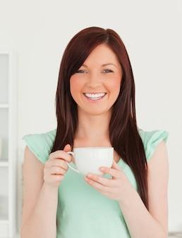Ładna miedzianowłosa kobieta ma jej śniadanie w kuchni