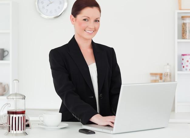 Ładna miedzianowłosa kobieta relaksuje z jej laptopem w kostiumu podczas gdy pozujący w kuchni