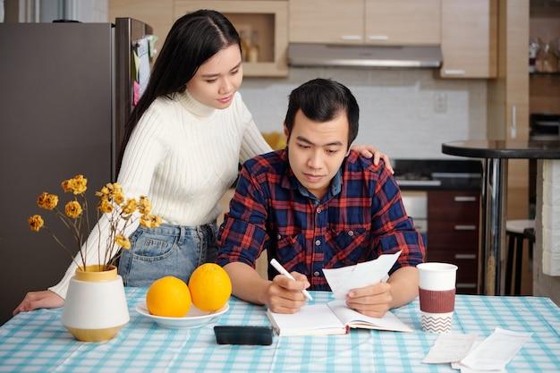 Ładna młoda azjatka patrząca na chłopaka sprawdzającego rachunki za media i pisząca sumę wydatków w terminarzu