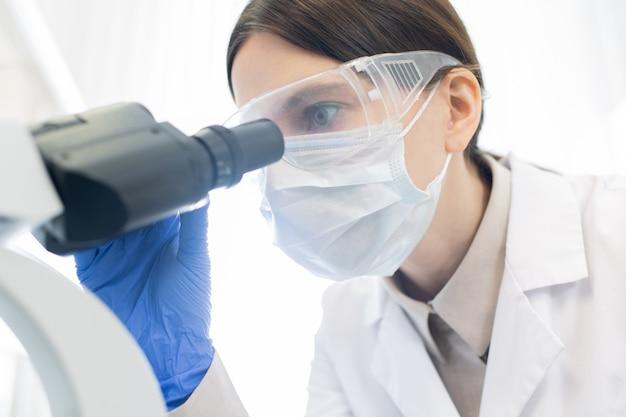 Ładna młoda badaczka w rękawiczkach, masce i okularach ochronnych pochyla się nad mikroskopem podczas badania nowego wirusa w laboratorium