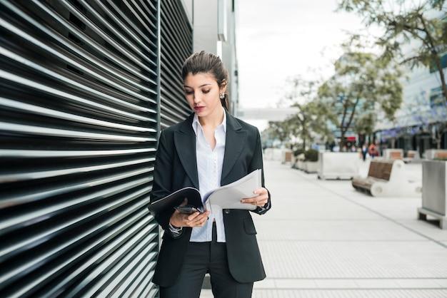 Ładna młoda bizneswoman pozycja blisko ściennego czytanie dokumentu w falcówce
