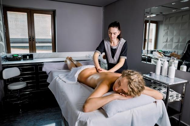 Ładna młoda blond caucasian kobieta dostaje z powrotem masaż w zdroju. kobieta klient otrzymujący profesjonalny masaż manualny w nowoczesnej gabinecie masażu w centrum medycznym