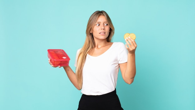 Ładna młoda blond kobieta trzyma tupperware