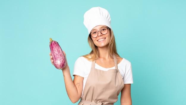Ładna młoda blondynka kucharz kobieta trzyma bakłażana