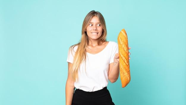 Ładna młoda blondynka trzyma bagietkę z chlebem