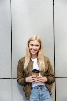 Ładna młoda blondynka trzyma filiżankę kawy