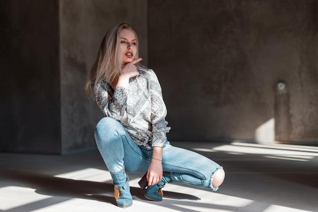 Ładna młoda blondynka w vintage stylowej koszuli w niebieskie modne zgrywanie dżinsów w zielonych modnych kowbojskich butach pozuje siedząc w pokoju z promieniami słonecznymi