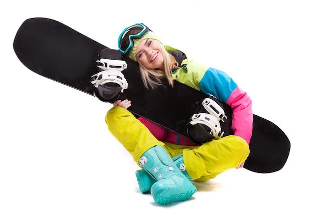 Ładna młoda blondynki kobieta w kolorowym śnieżnym kostiumu siedzi ze skrzyżowanymi nogami