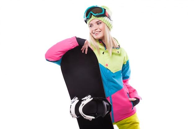 Ładna młoda blondynki kobieta w kolorowym śnieżnym żakiecie trzyma snowboard