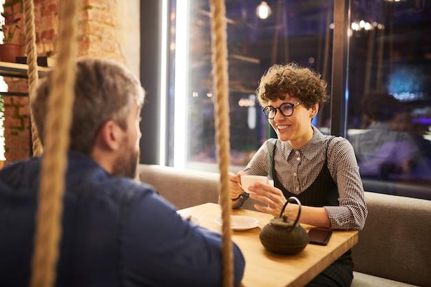 Ładna młoda brunetka kobieta w elegancki dorywczo filiżankę herbaty podczas rozmowy ze swoim chłopakiem w przytulnej kawiarni lub restauracji