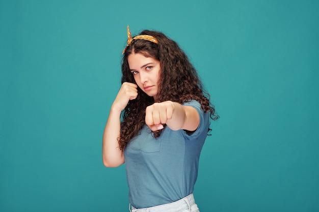 Ładna młoda brunetka kobieta z długimi falującymi włosami, patrząc na ciebie i pokazując poncz podczas walki z niebieską ścianą