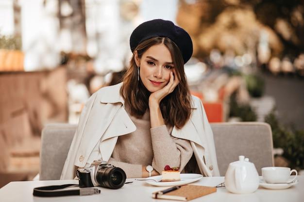 Ładna młoda brunetka z beretem, trenczem i beżowym swetrem, siedząca przy stole z filiżanką herbaty, sernikiem, notatnikiem i aparatem na tarasie kawiarni w ciągu dnia