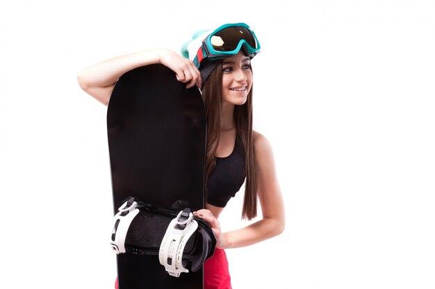 Ładna młoda brunetki kobieta w czerń krótkim podkoszulku bez rękawów trzyma snowboard