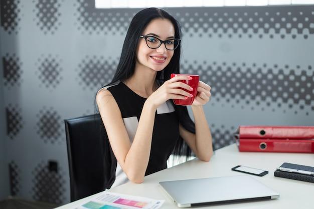Ładna, młoda businesslady w czarnej sukni i okularach siedzi przy stole i trzyma czerwony kubek
