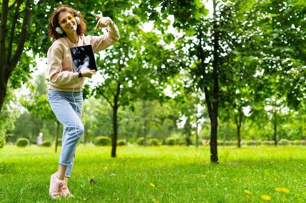 Ładna młoda caucasian kobieta angażuje się w freelance w parku z laptopem