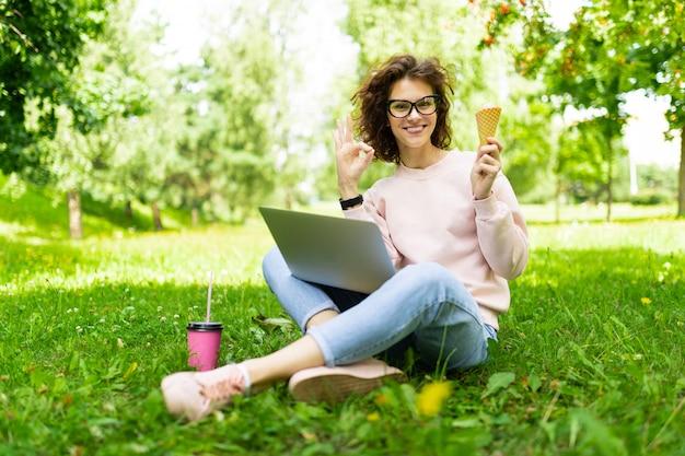 Ładna młoda caucasian kobieta iść na spacer przy parkiem z kawą i laptopem