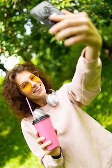 Ładna młoda caucasian kobieta iść na spacer w parku z filiżanką kawy i pokazuje jej telefon