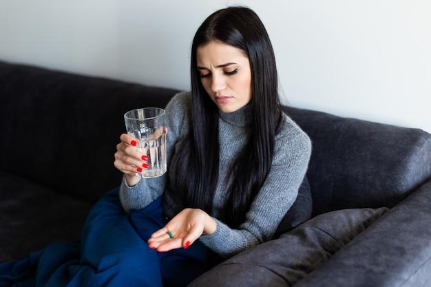 Ładna młoda chora kobieta trzyma ranek po pigułki i szklanki wody w domu