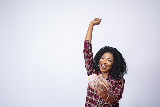 Ładna młoda czarna kobieta trzymająca zwitek gotówki, wyrażająca swoje podekscytowanie