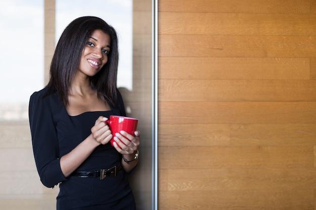 Ładna, młoda dama biznesu w czarnym mocnym apartamencie posiada czerwony kubek