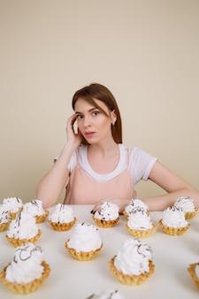 Ładna młoda dama pozuje podczas gdy siedzący blisko babeczek na stole