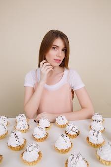 Ładna młoda dama siedzi i pozuje blisko babeczek na stole
