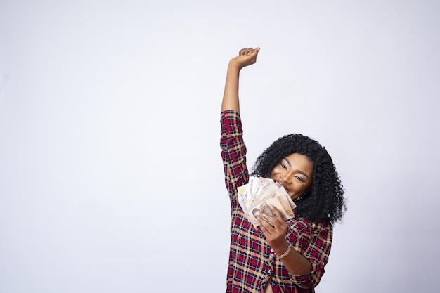 Ładna młoda dama trzymająca pieniądze i świętująca przed białą ścianą