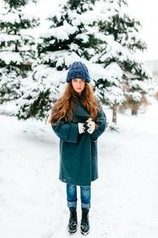 Ładna młoda długowłosa brunetka pozuje w śnieżnym zima parku