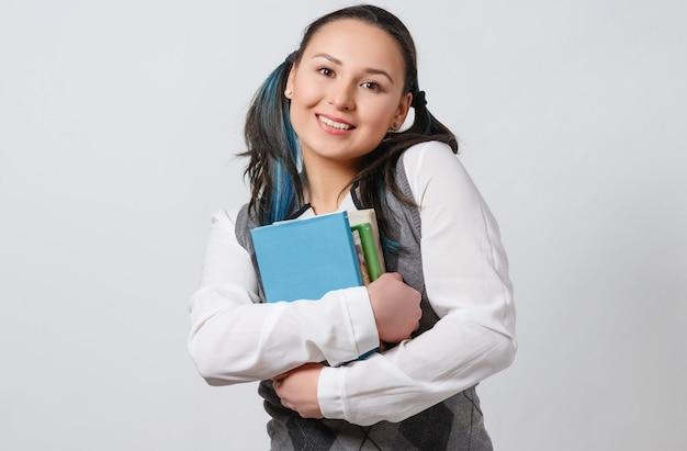 Ładna, młoda dziewczyna jest uczennicą liceum, trzymając przed sobą stos podręczników.
