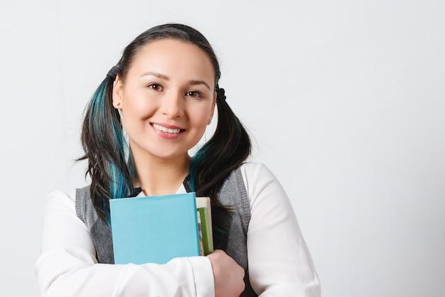 Ładna młoda dziewczyna jest uczennicą liceum ze stosem podręczników w rękach. na białym tle