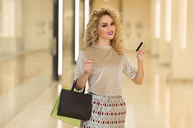 Ładna młoda dziewczyna pokazując kartę kredytową w centrum handlowym
