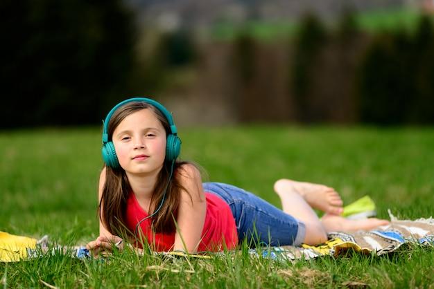 Ładna młoda dziewczyna słucha muzyki w naturze