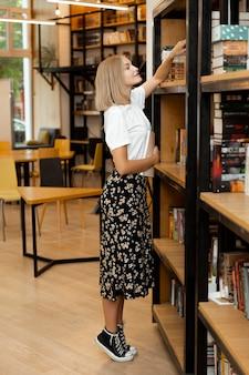 Ładna młoda dziewczyna szuka książki