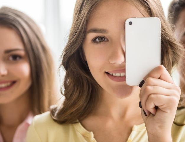 Ładna młoda dziewczyna trzyma jej mądrze telefon.