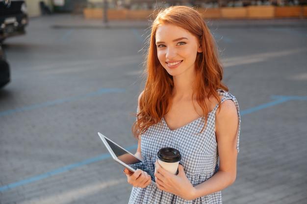 Ładna młoda dziewczyna trzyma komputer osobisty pastylkę i filiżankę kawy