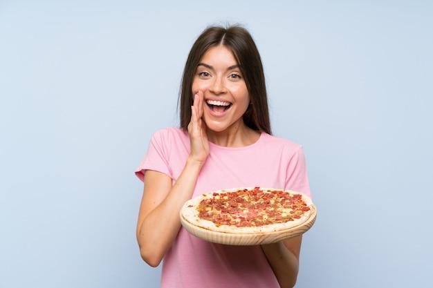 Ładna młoda dziewczyna trzyma pizzę nad odosobnioną błękit ścianą z niespodzianką i szokującym wyrazem twarzy