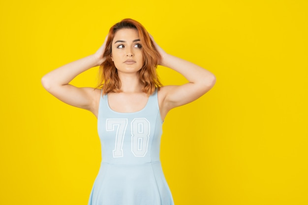 Ładna młoda dziewczyna trzyma ręce na włosach i odwraca wzrok