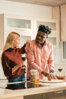 Ładna młoda dziewczyna uśmiecha się do swojego szczęśliwego chłopaka i kładzie jedną rękę na jego ramieniu, trzymając kieliszek wina i obserwując, jak ugniata ciasto