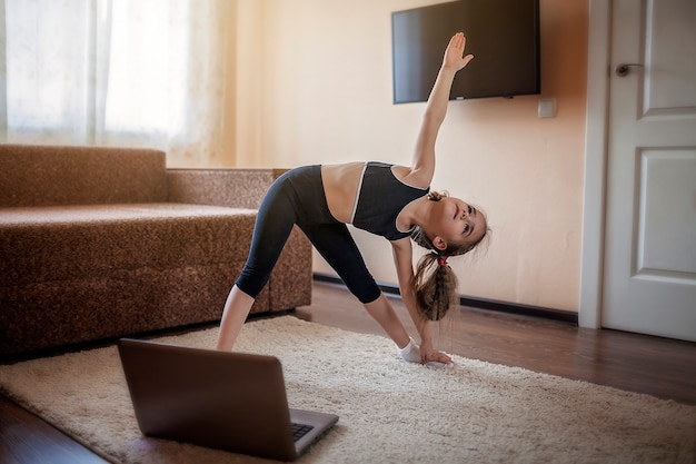Ładna młoda dziewczyna w odzieży sportowej, oglądając wideo online na laptopie i ćwiczeń fitness w domu