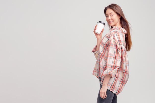 Ładna młoda dziewczyna w zwykłym ubraniu uśmiecha się słodko i trzyma szklankę kawy w jednorazowym opakowaniu.