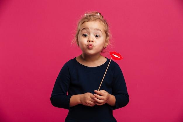 Ładna młoda dziewczyna wysyła pocałunek powietrza i trzymając papierowe usta