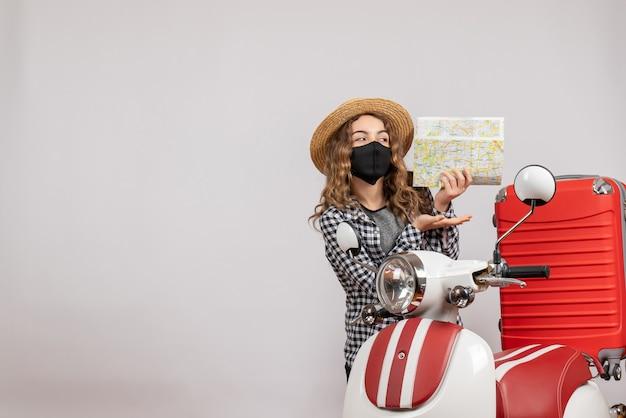 Ładna młoda dziewczyna z czarną maską trzymająca mapę stojącą w pobliżu czerwonego motoroweru